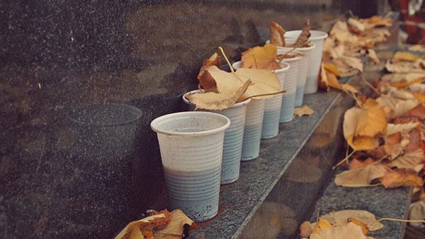 plastične čaše sa kafom na spomeniku na groblju