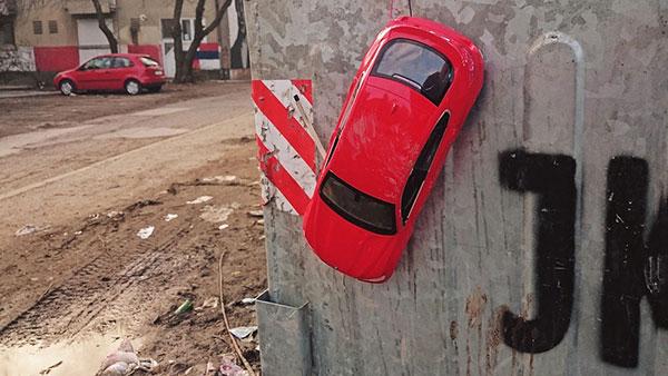 crveni automobilčić zakačen za kontejner