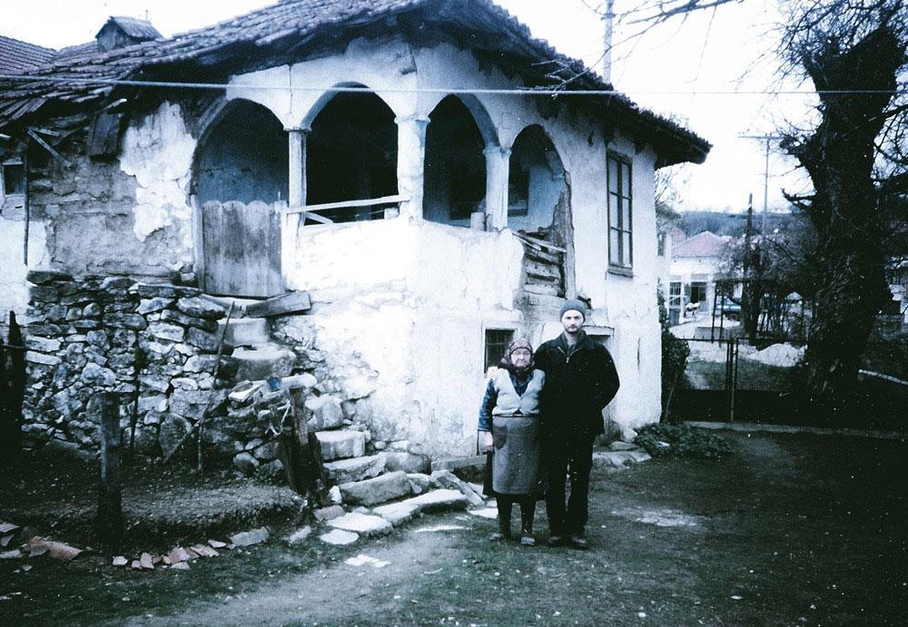 crno-bela fotografija: starica i mladić ispred stare kuće