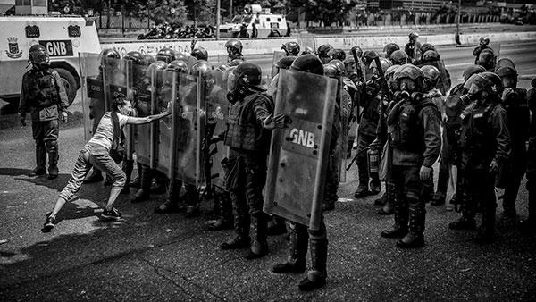 Žena pokušava da zaustavi pripadnike Nacionalne garde tokom antivladinog protesta, 2017.