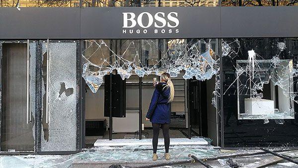 Žena fotografiše razbijeni izlog Hugo Boss radnje