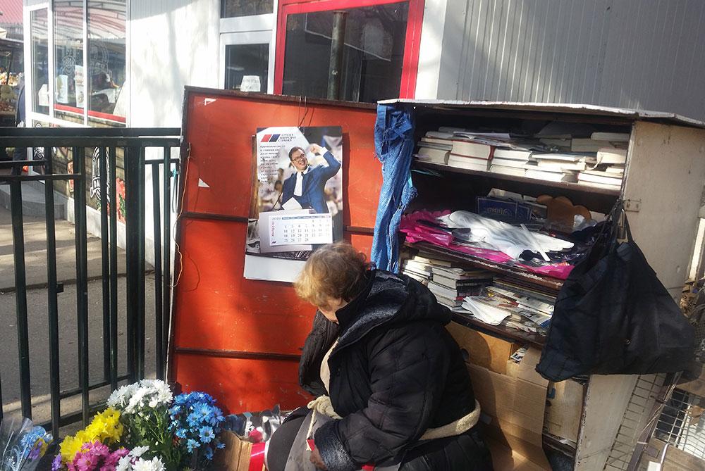 žena na pijaci prodaje cveće, a iza nje je kalendar sa likom Vučića