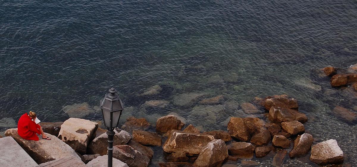 Žena sedi na obali mora i čita knjigu, Trst
