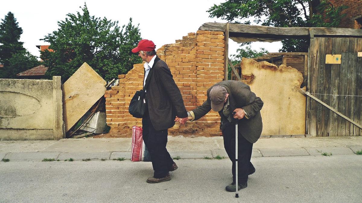 Dva starca, otac i sin, hodaju ulicom držeći se za ruku