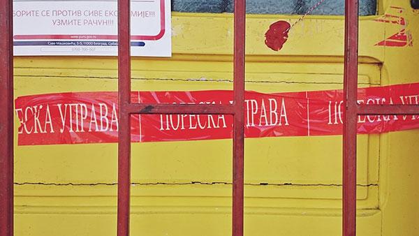 Crvena traka Poreske uprave zalepljena na vratima zatvorene radnje