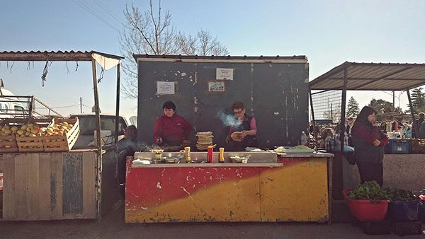 Dve žene na tezgi na pijaci spremaju pljeskavice