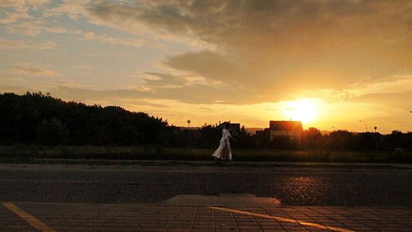 žena u beloj haljini u daljini u sumrak
