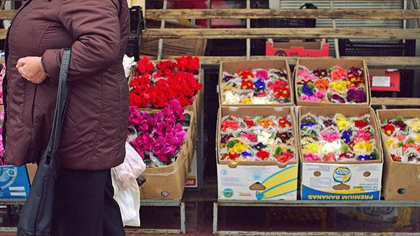 žena prolazi pored tezge sa cvećem