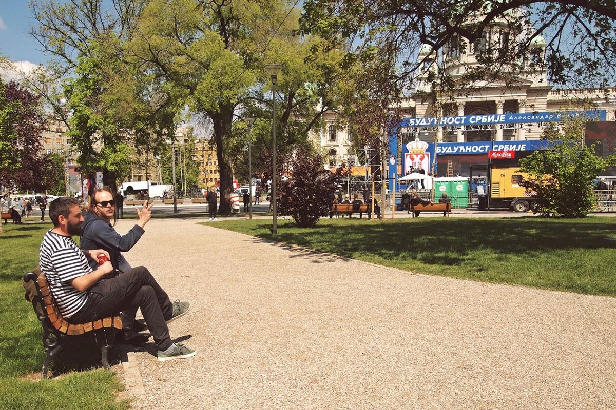 Dva čoveka sede u Pionirskom parku na klupi tokom kontramitinga vlast 19.04.2019.