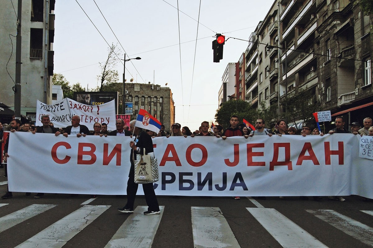 čovek prelazi ulicu na pešačkom prelazu ispred transparenta protesta Svi kao jedan