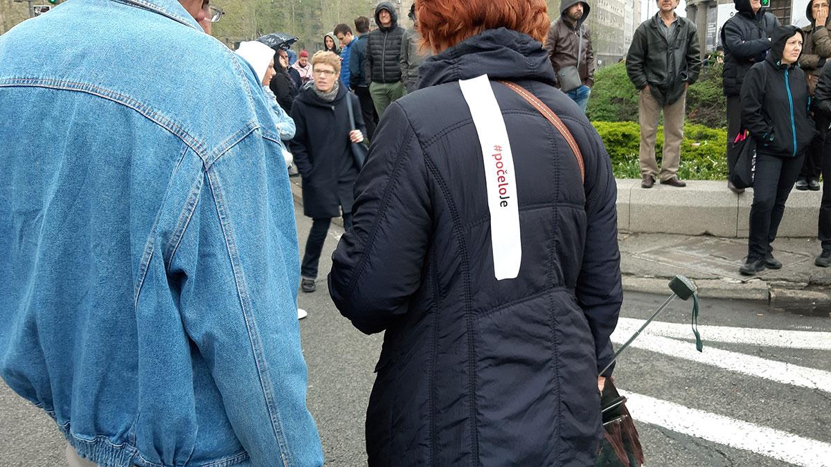 Nalepnica #počelo je nalepljena na leđima žene