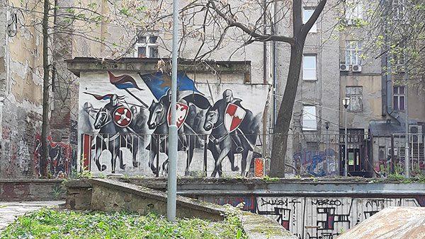 Mural na zidu zgrade na kojem su tri konjanika u viteškoj opremi