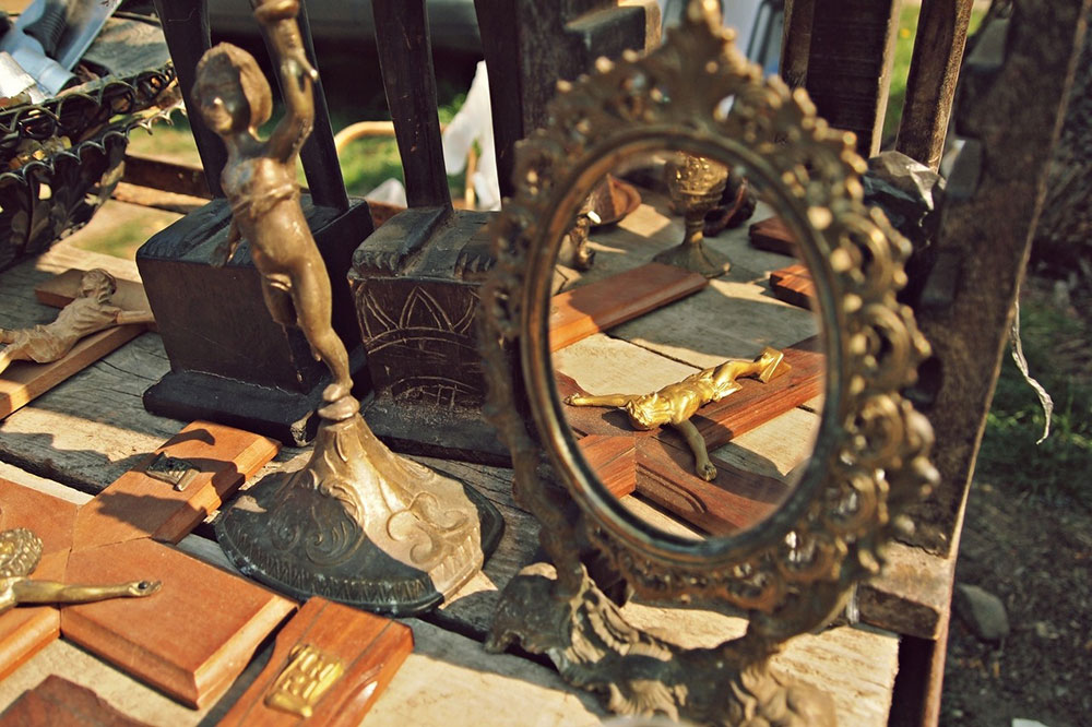 ogledalo na buvljaku u kojem se vidi odraz Krista razapetog na krst