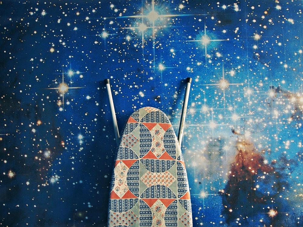 Daska za peglanje naslonjena uz zid na kojem je foto-tapet sa univerzumom