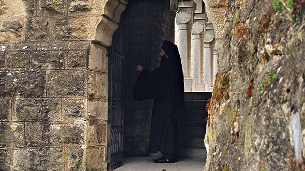sveštenik ispred vrata crkve