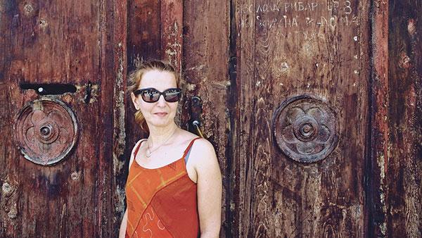 žena ispred drvenih vrata