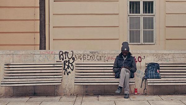 čovek sedi na klupi