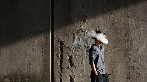 čovek u dimu cigarete