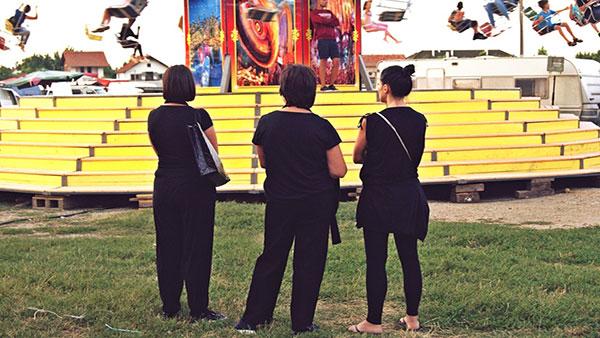 Tri žene posmatraju decu na ringišpilu