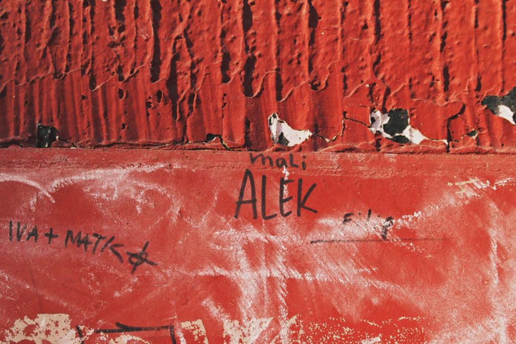 Natpis na crvenom zidu: Mali Alek