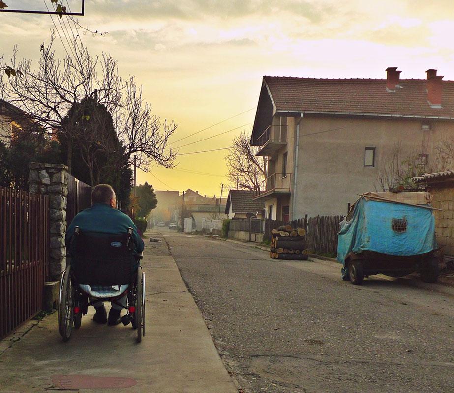 čovek u invalidskim kolicima na ulici