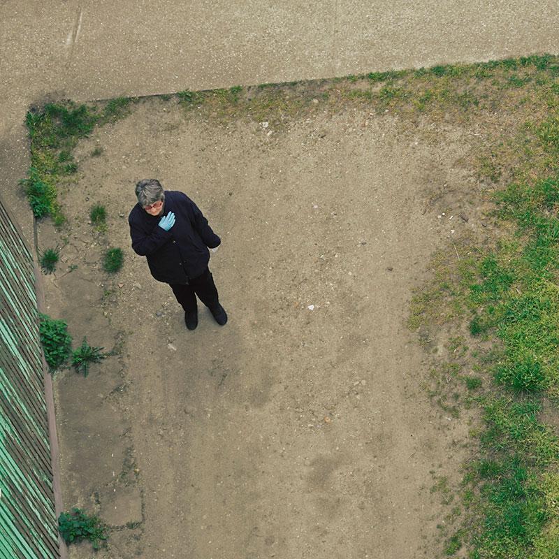 Starija žena sama stoji u nekom dvorištu