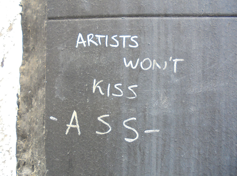 Natpis na zidu: Artists won't kiss ass