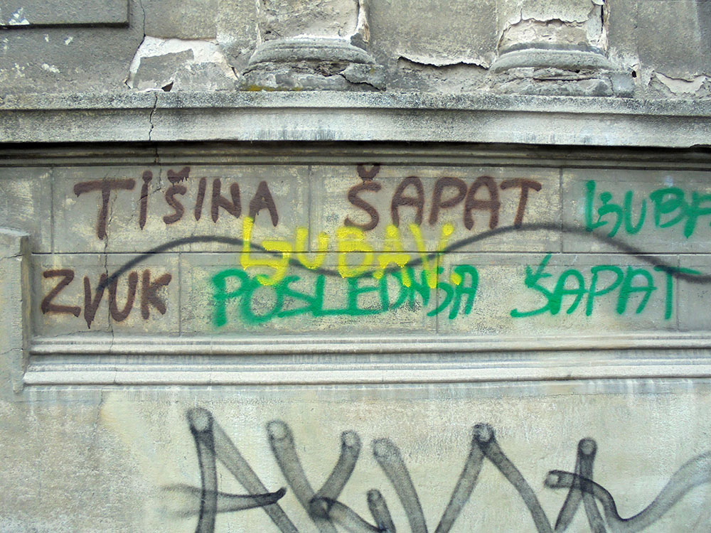 Sprejem u boji na fasadi zgrade ispisano: tišina, šapat, zvuk, poslednji šapat, ljubav