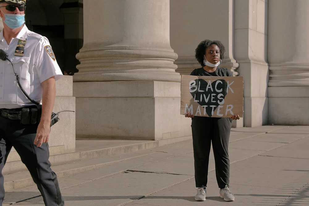 Žena drži transparent Black lives matter
