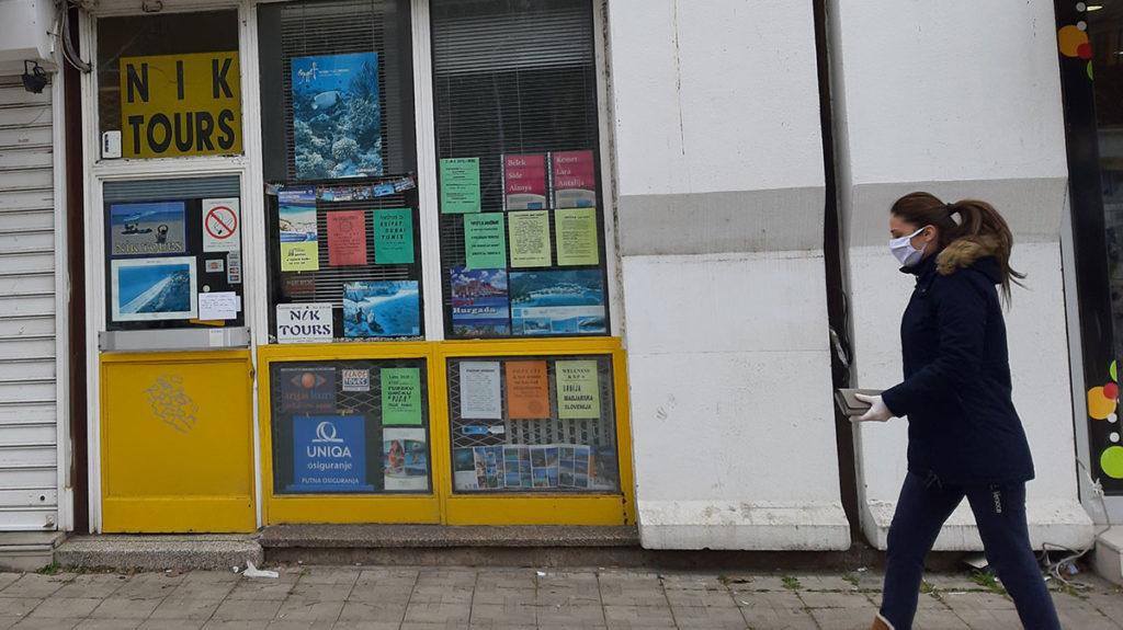 Devojka sa maskom na licu prolazi pored zatvorene turističke agencije