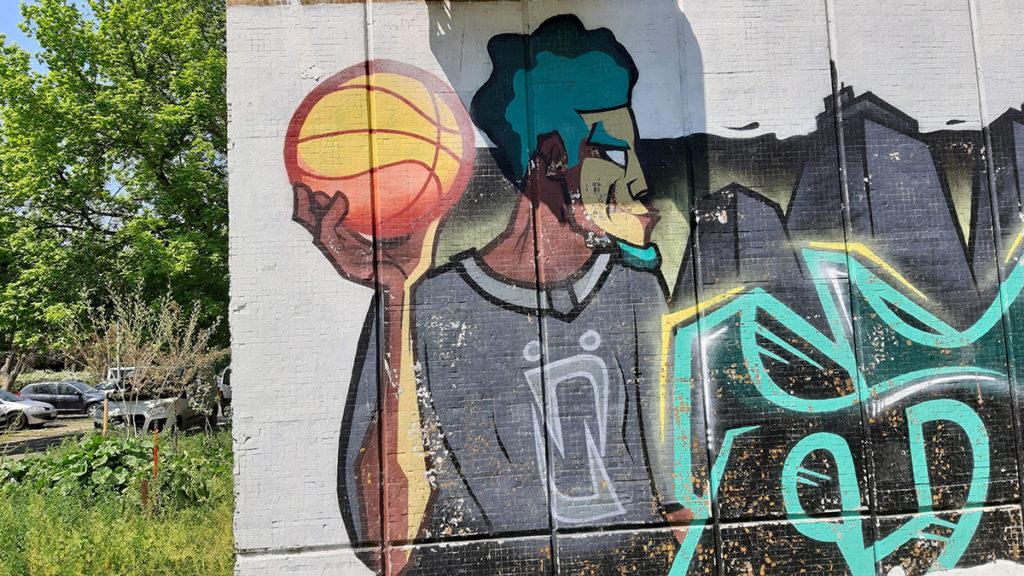 Mural na kojem je nacrtan čovek koji u ruci drži košarkašku loptu