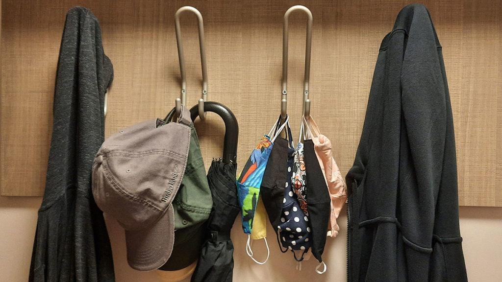 čiviluk na kojem su osim odeće i kišobrana obešene i zaštitne maske za lice