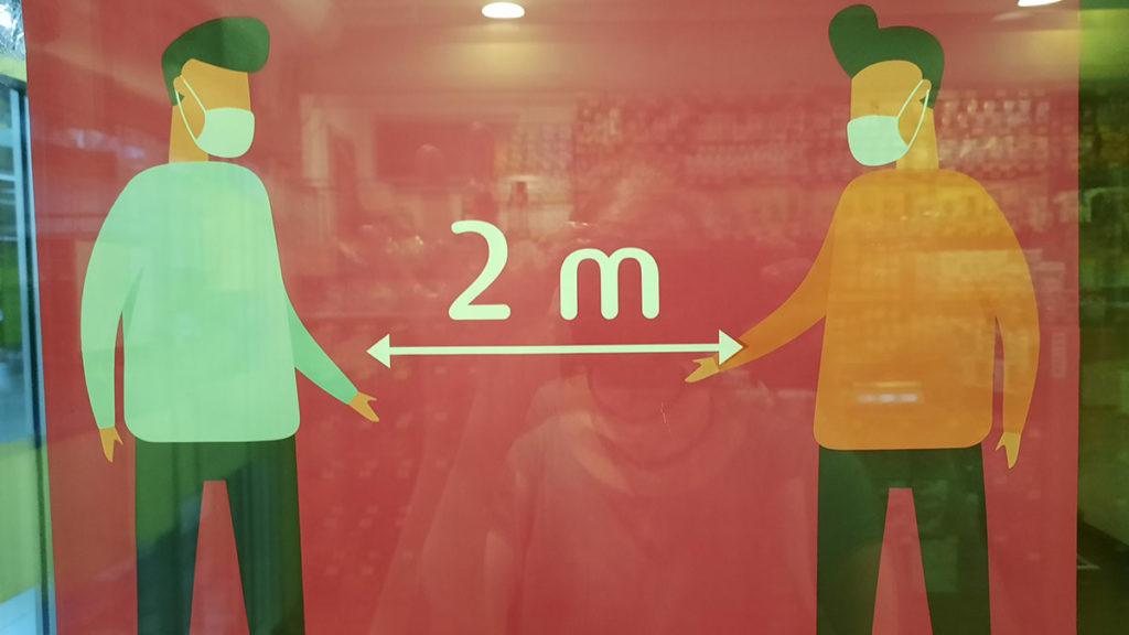 Plakat koji pokazuje 2 metra rastojanja koje treba održavati između ljudi