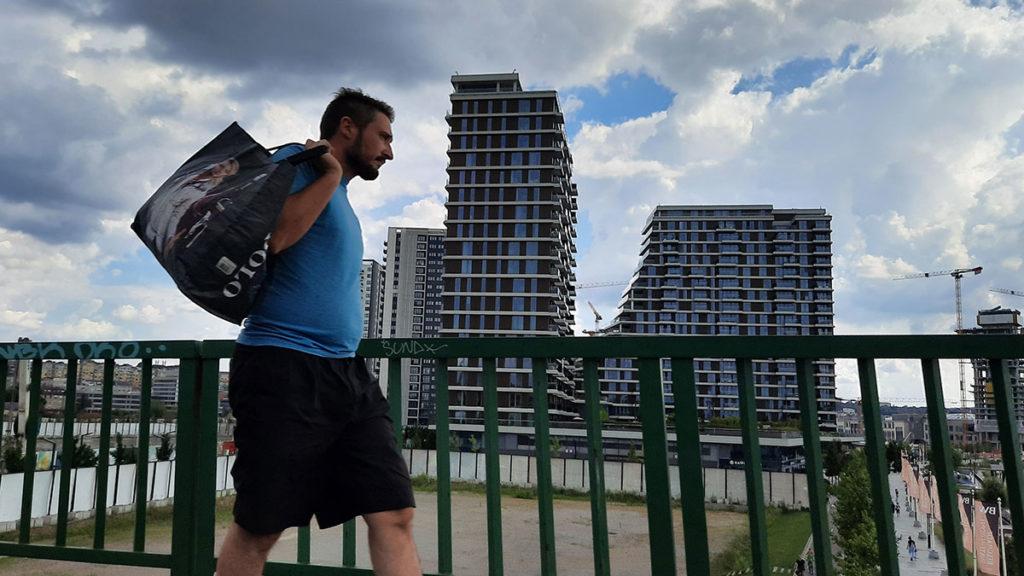 čovek sa torbom na leđima prolazi pored zgrada Beograda na vodi