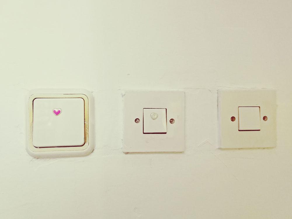 tri prekidača za svetlo na zidu
