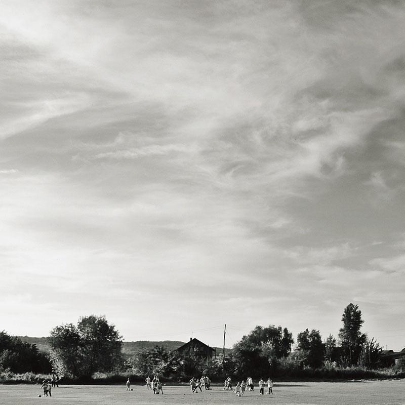 Deca igraju fudbal na poljani, crno-bela fotografija