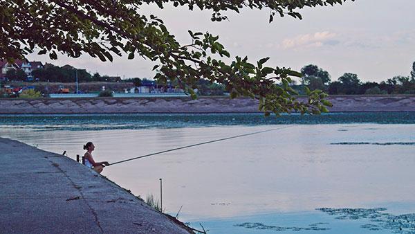 žena peca na obali reke