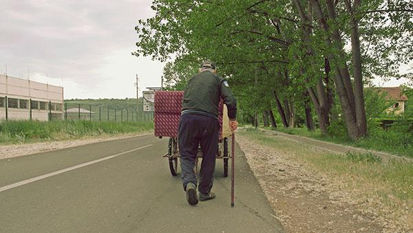 starac sa štapom u ruci gura krevet na nekakvim kolicima