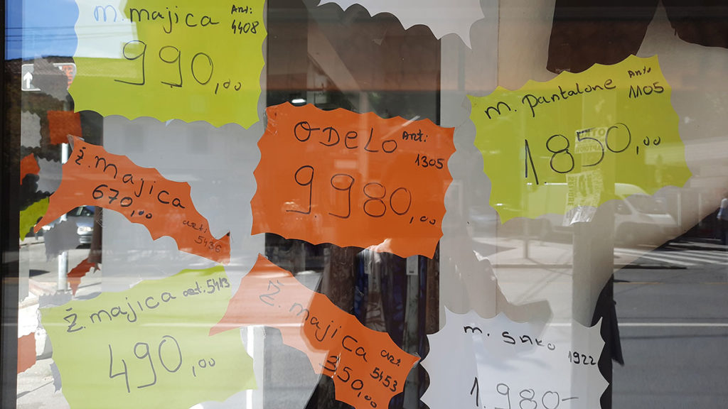 izlog prodavnice u kome se vide ispisane cene robe