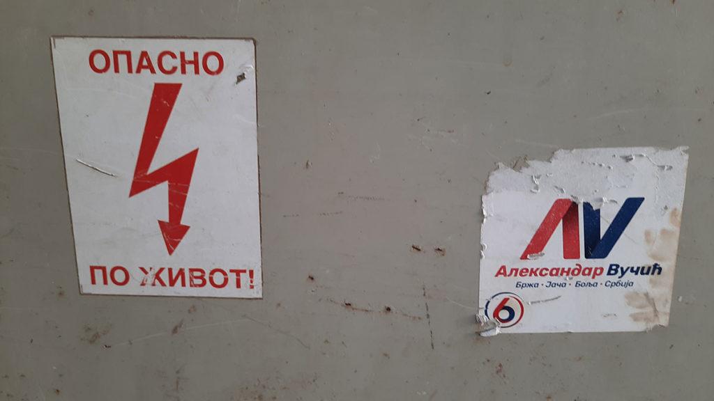 znak Opasno po život pored nalepnice za izbor Aleksandra Vučića