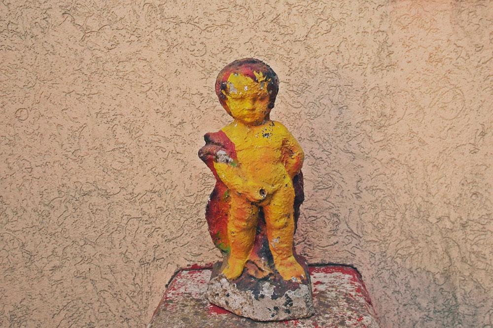 ukrasna skulptura dečaka koji piša
