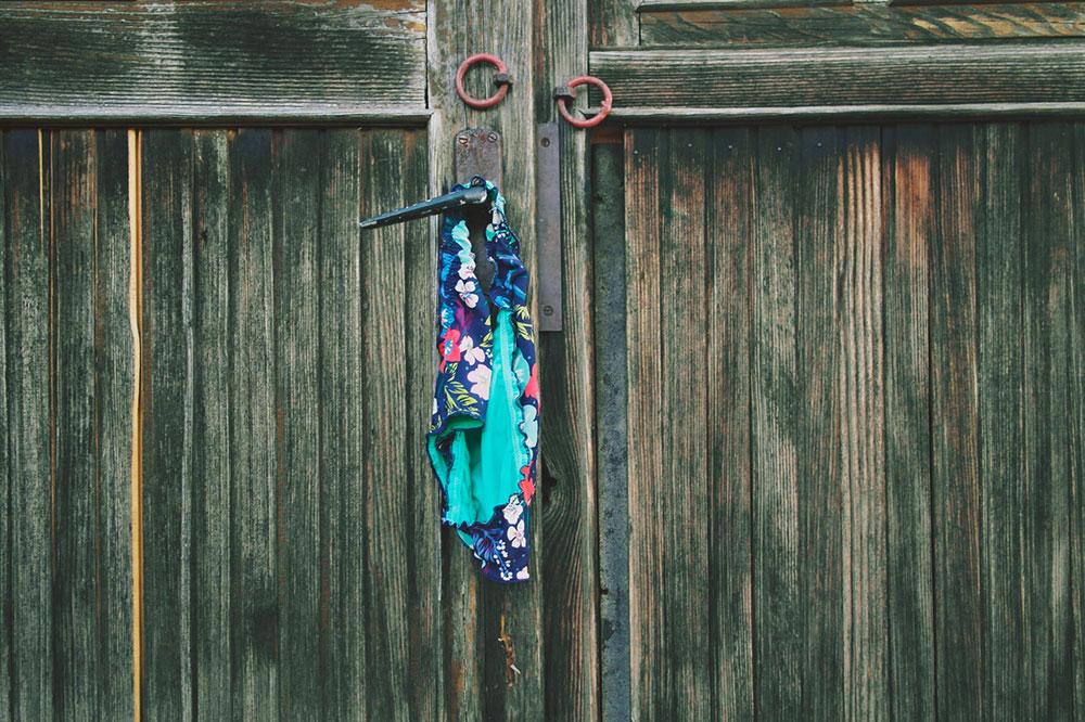 ženske kupaće gaćice okačene na kvaku drvenih vrata