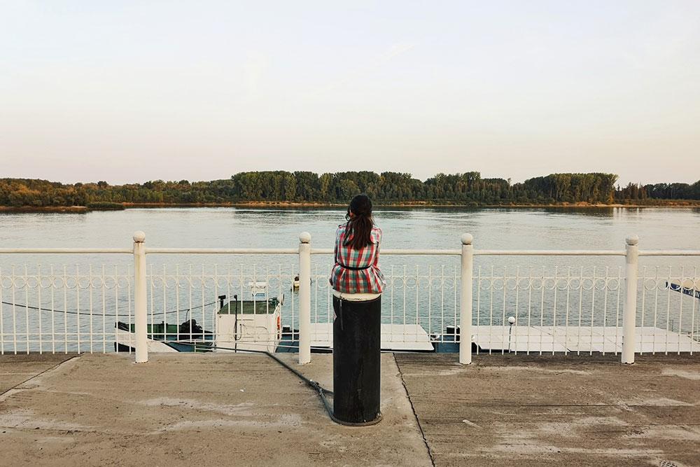 žena sedi na obali reke