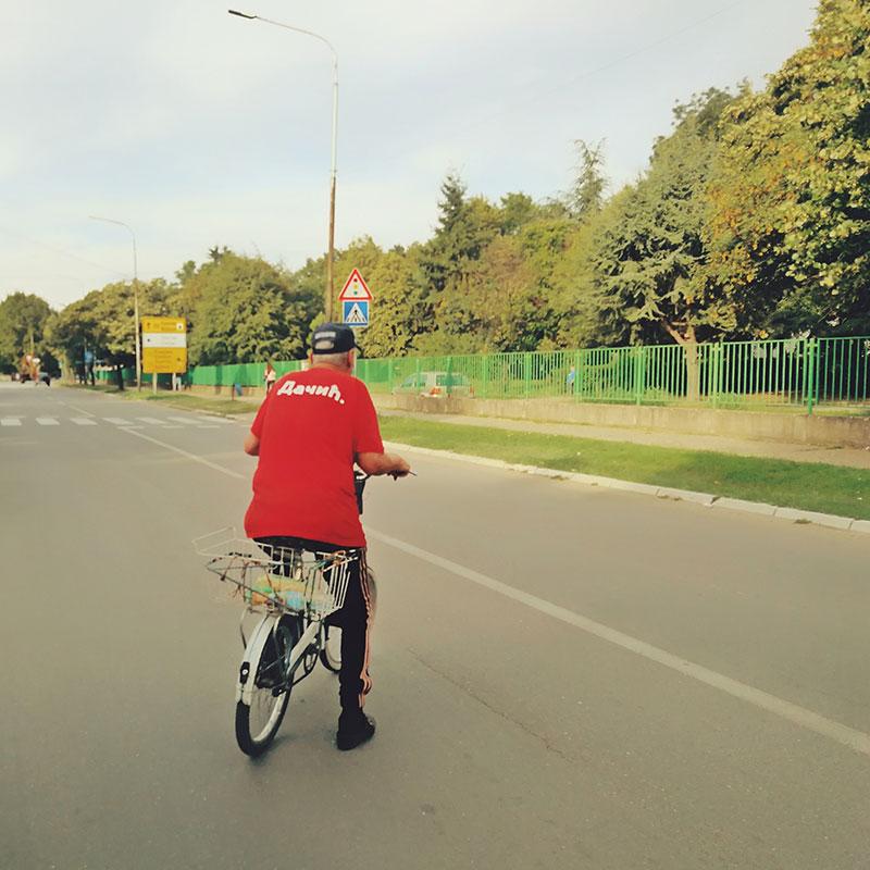 Čovek na biciklu, na majici mu piše Dačić