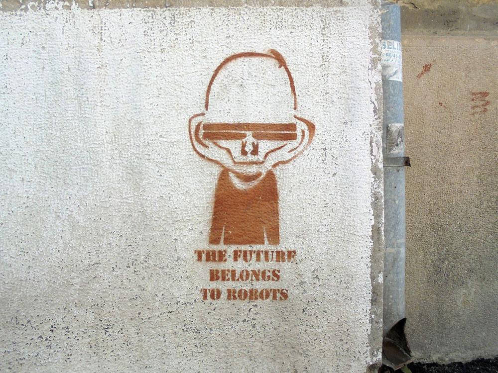 Stensil sa natpisom na engleskom:  Budućnost pripada robotima