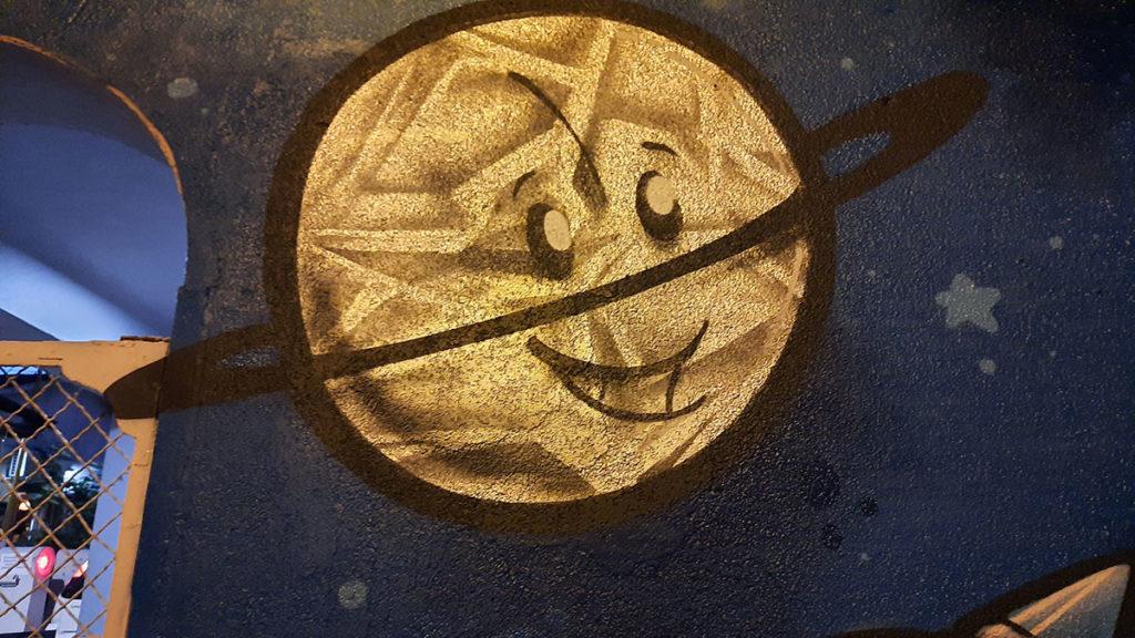 nactrtana planeta sa prstenom koja se smeje