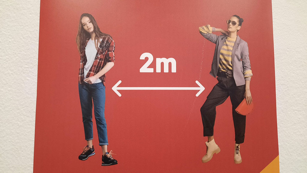 plakat na kome je označen razmak od 2 metra između dve žene