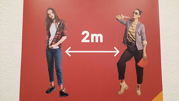 Plakat za razmak od 2 metra izmeću 2 žene