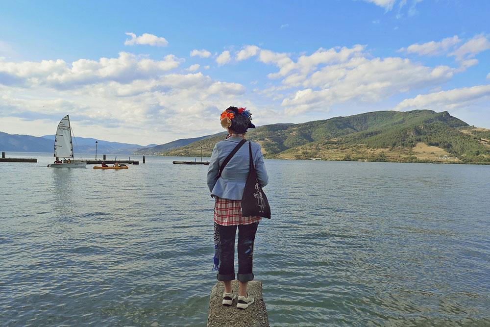 žena stoji na obali jezera