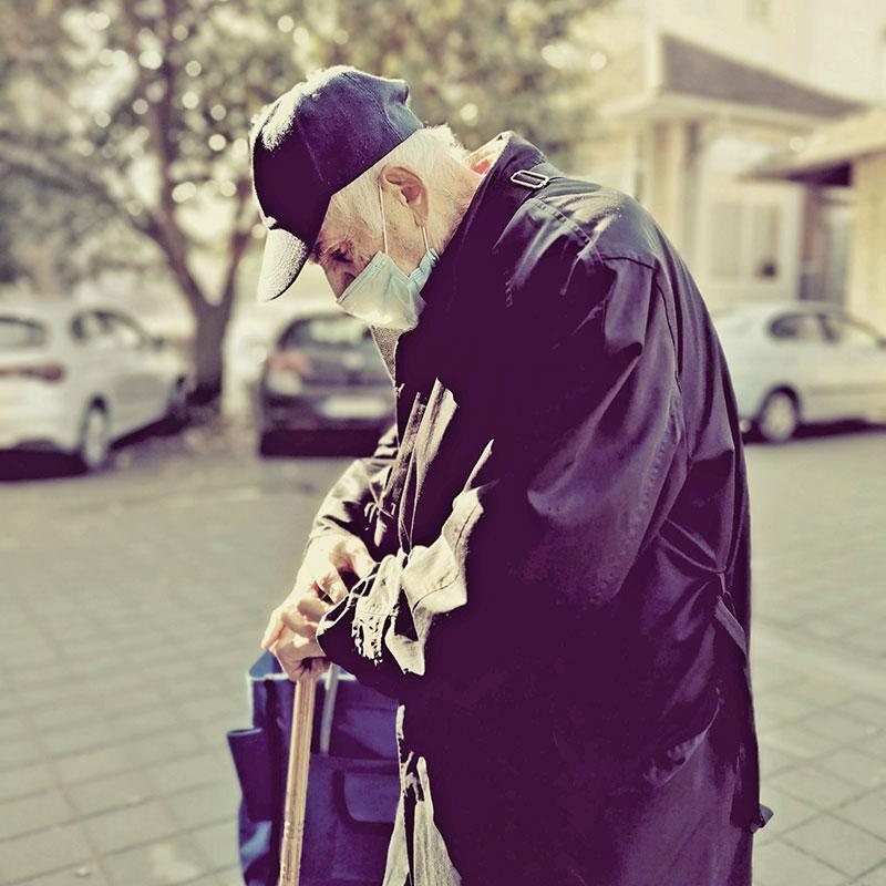 Starac na ulici sa maskom na licu
